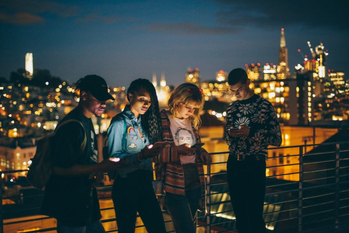 Young people at night looking at mobile phones
