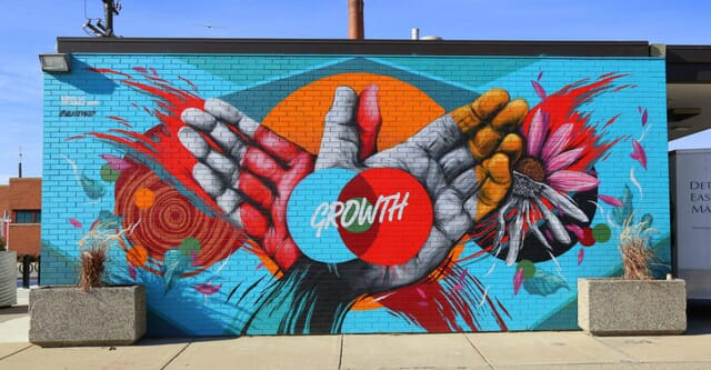 """Painting on brick wall depicting hands and word """"growth"""""""