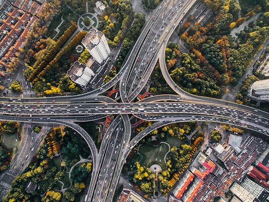 Overhead shot of a large 4-way highway intersection with busy traffic