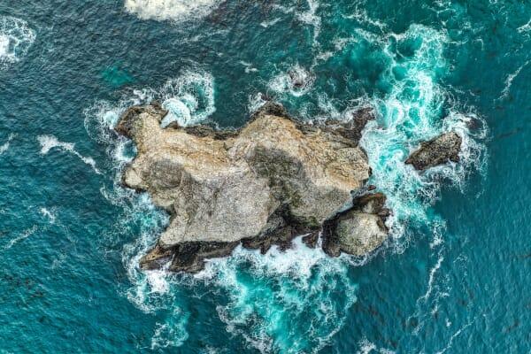 Aerial shot of a rock in the ocean in Big Sur