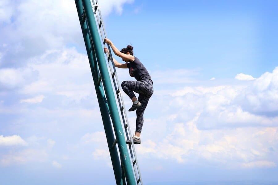 wWoman climbing metal ladder