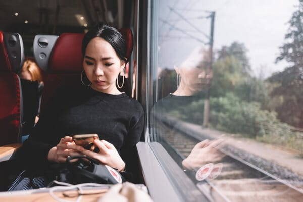 asian-woman-using-mobile-phone-on-the-train-while-traveling_t20_P3PJYR