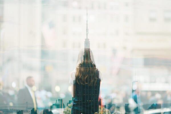 women reflective glass city scene