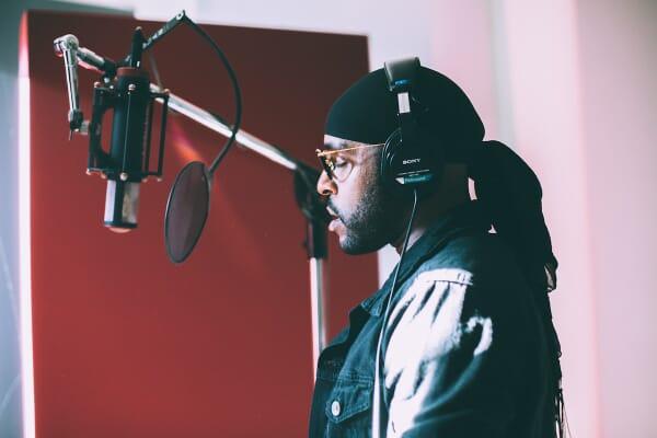 Verse Simmonds singing infront of condenser microphone