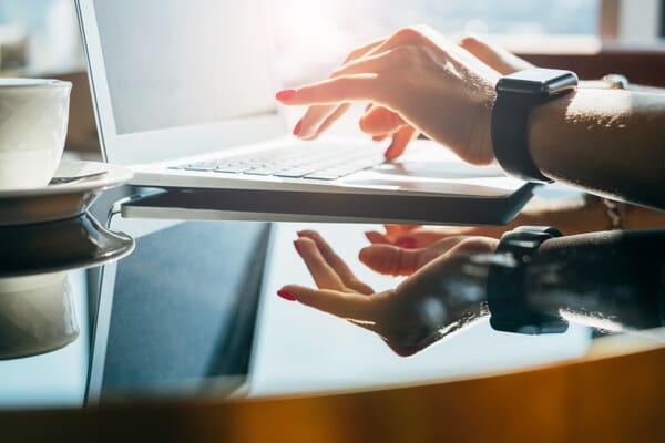 Woman's typing wearing apple watch